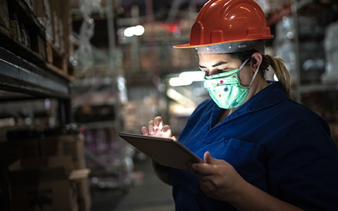 woman in mask and hard hat in a warehouse on her tablet