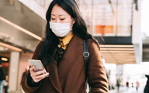 woman outside wearing a face mask while looking at her phone