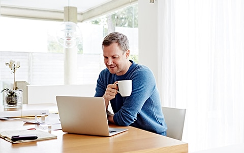 man sitting at his home table on his laptop and having a cup of coffee