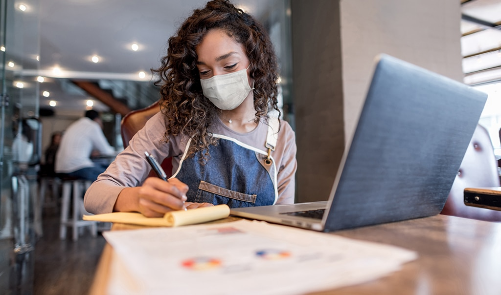 woman sitting at table in cafe with laptop and financial paperwork in front of her as she writes on a notepad. How to Protect Your New Business