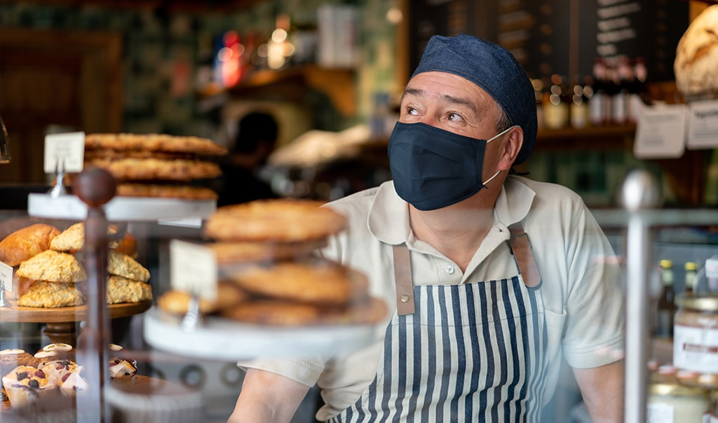 man behind a bakery counter wearing a face mask. How to Scale Products and Services To Increase Profitability