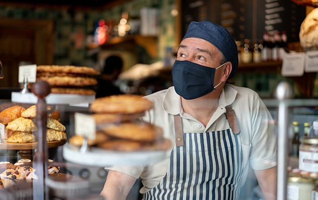 man wearing mask, hat and masks stands behinde a bakery counter, How to Scale Products and Services To Increase Profitability