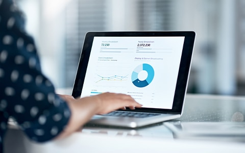 woman on computer at desk looking at financials, How to Get Funding to Grow a Business
