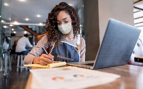 woman sitting at table at cafe in mask and apron looking at laptop and business paperwork, How to Protect Your New Business