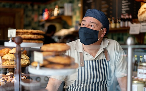 man in mask and apron standing behind bakery counter, How to Scale Products and Services to Increase Profitability