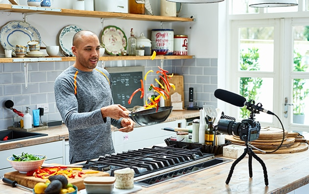 man cooking at home in front of a camera for online viewing