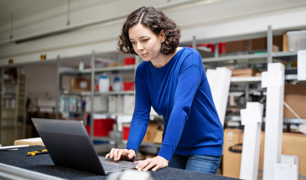 woman standing up working on laptop computer