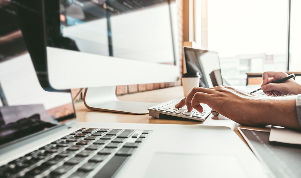 Image of a pair of hands. One hand works on a computer while the other writes notes. How to Accelerate New Digital Ways of Working in Your Business