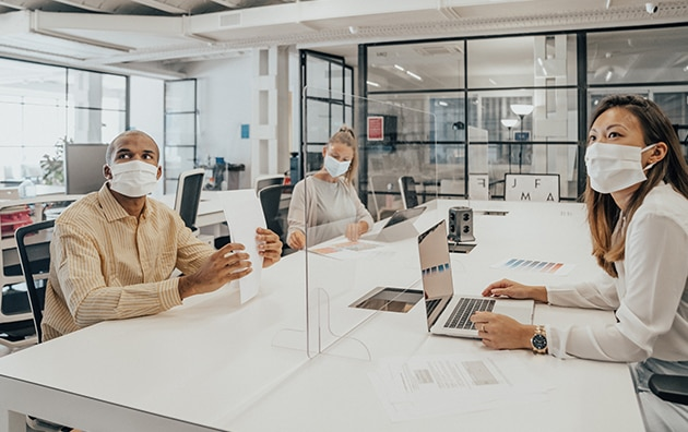 Office workers sitting at a shared workspace. They are all wearing face masks. There is a plexiglass divider in the middle of the table. How to Approach Agile Decision Making in Your Organization
