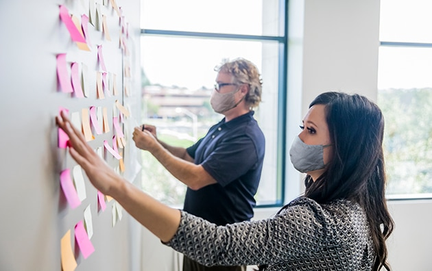 A man and a woman working to organize a wall of sticky notes. Rethinking Roles Post-Pandemic