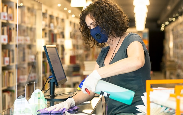 Retail store clerk wearing a face mask is spraying and wiping down the counter with plexiglas affixed to it. Tips for Busines Process Improvement