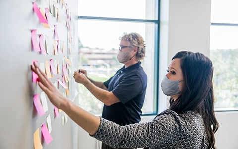 A man and a woman working to organize a wall of post it notes. Rethinking Roles Post-Pandemic