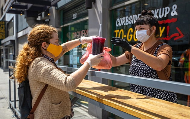 two women wearing masks and gloves. One woman is handing a restaurant to go order to another woman