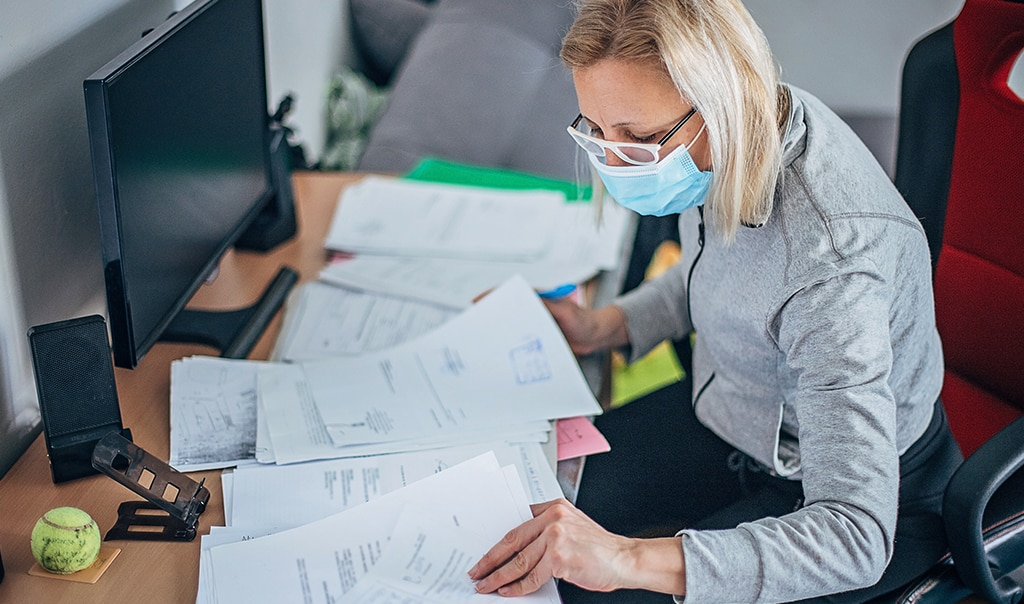 business owner wearing mask assessing papers