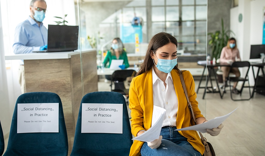 Woman with mask on sitting in waiting room