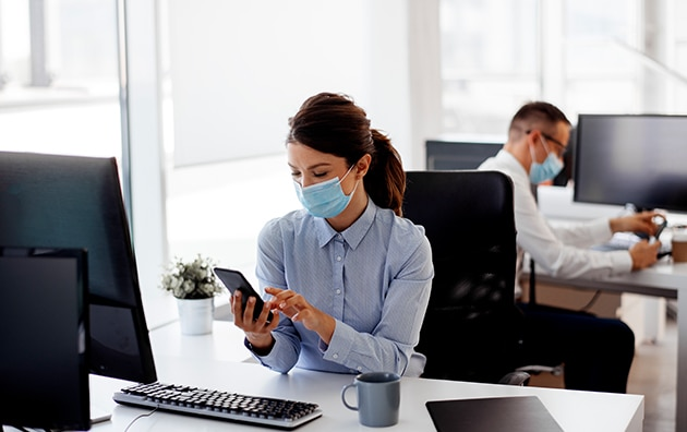 two people working in the office while wearing masks. How to Keep Your Employees Save in the Workplace During COVID-19
