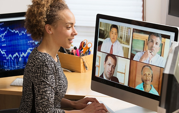 A woman sits at desk at home on a video conference call. Managing Remote Workers During COVID-19