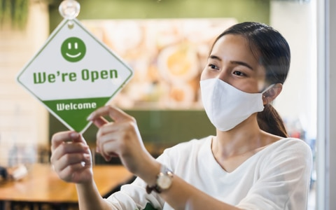 woman hanging open sign in doorway as she wears a mask