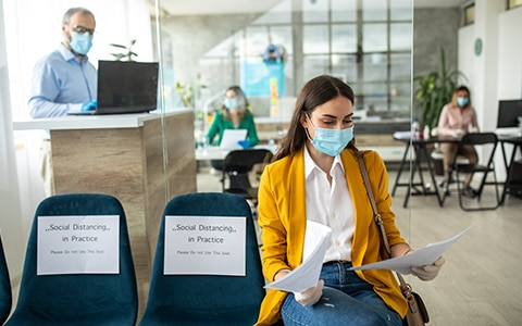 woman sitting in waiting room at clinic wearing a mask and gloves, How to Improve Employee Health, Wellness and Well Being