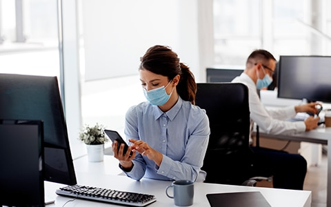 workers at their desks in the office who are wearing masks. How to Keep Your Employee Safe in the Workplace During COVID-19