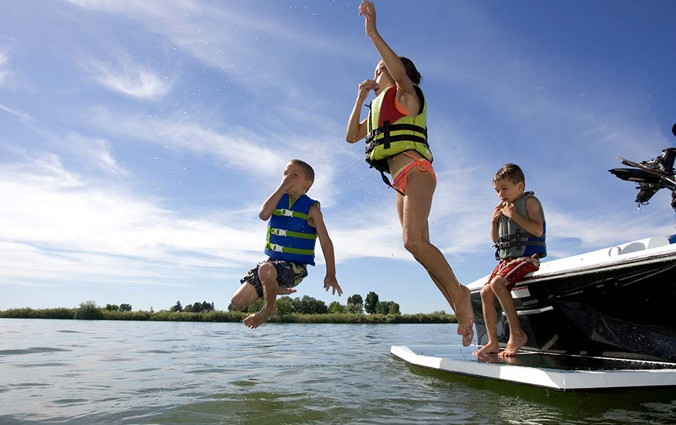 Three kids jumping into the water from a boat