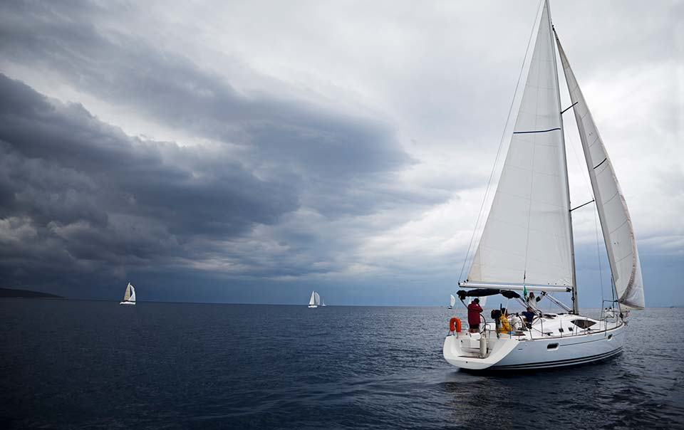 Boat sailing away from oncoming storm