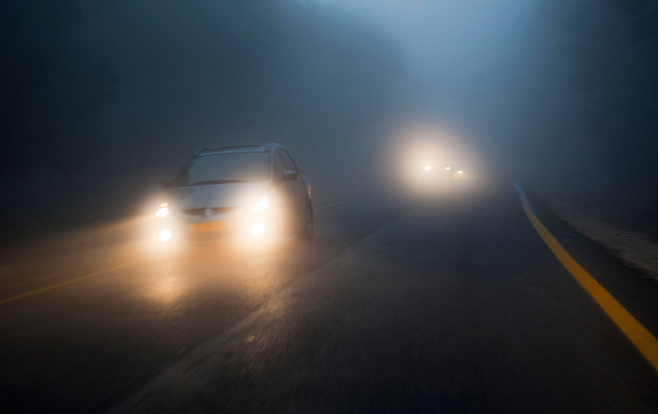 Car driving in fog at night with headlights on