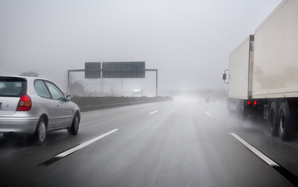 cars and trucks driving in heavy rain and wind