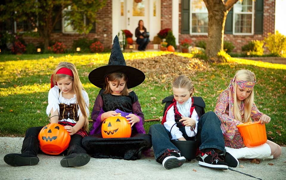Kids in Halloween costumes sitting on the sidewalk