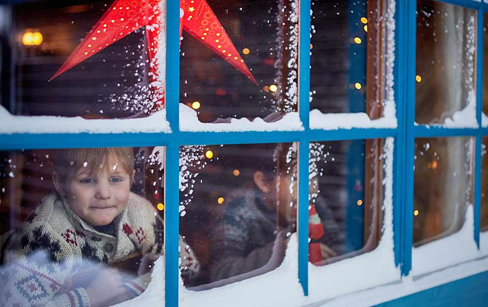 Two children looking out snowy window