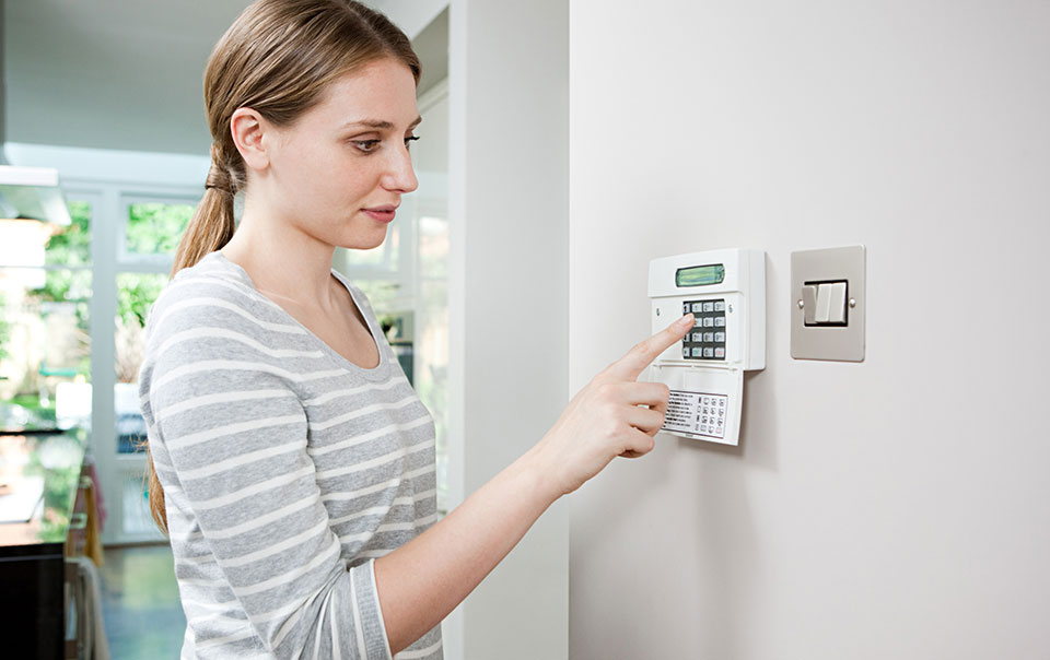 Woman punching in numbers to alarm security system