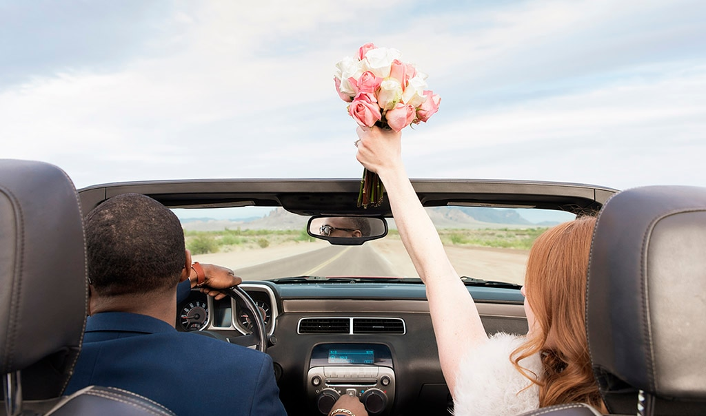 Husband and wife driving off in a convertible car after getting married