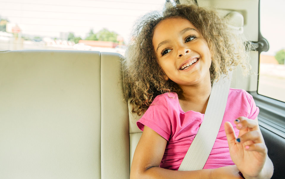 Child sitting safely in the back seat