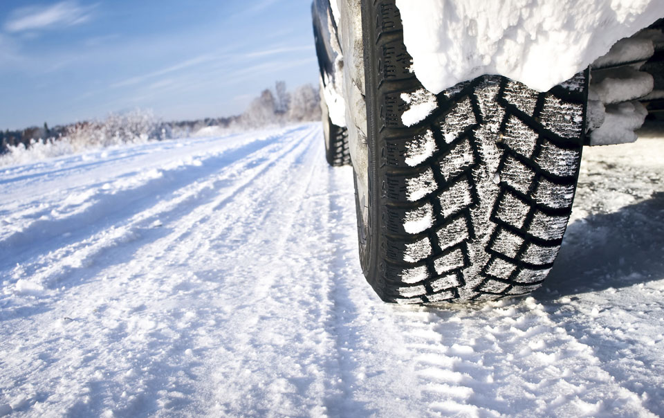 Close-up of snow tires on snow-covered road