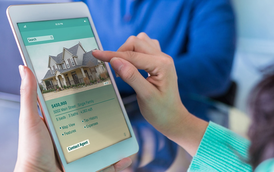person viewing home listings online, pros and cons of buying a house now