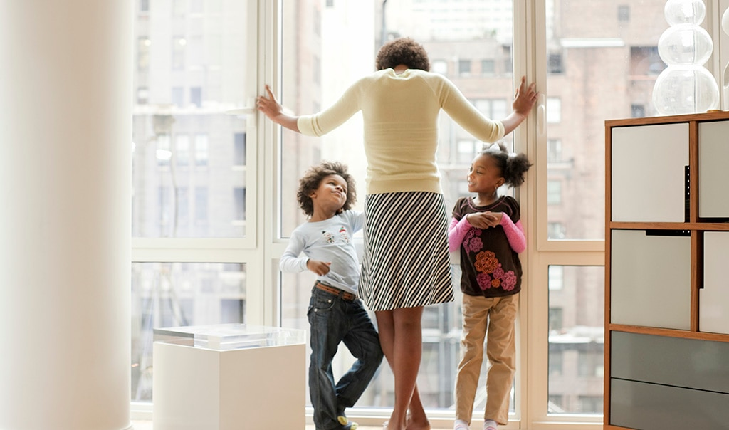 Woman standing with kids looking out window of condo