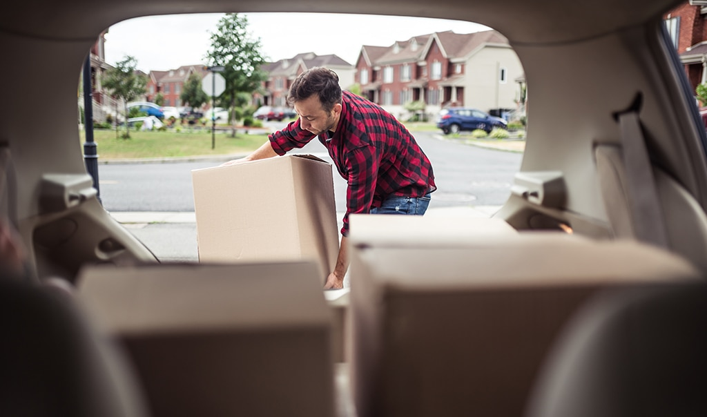 man packing his car for moving out of his home