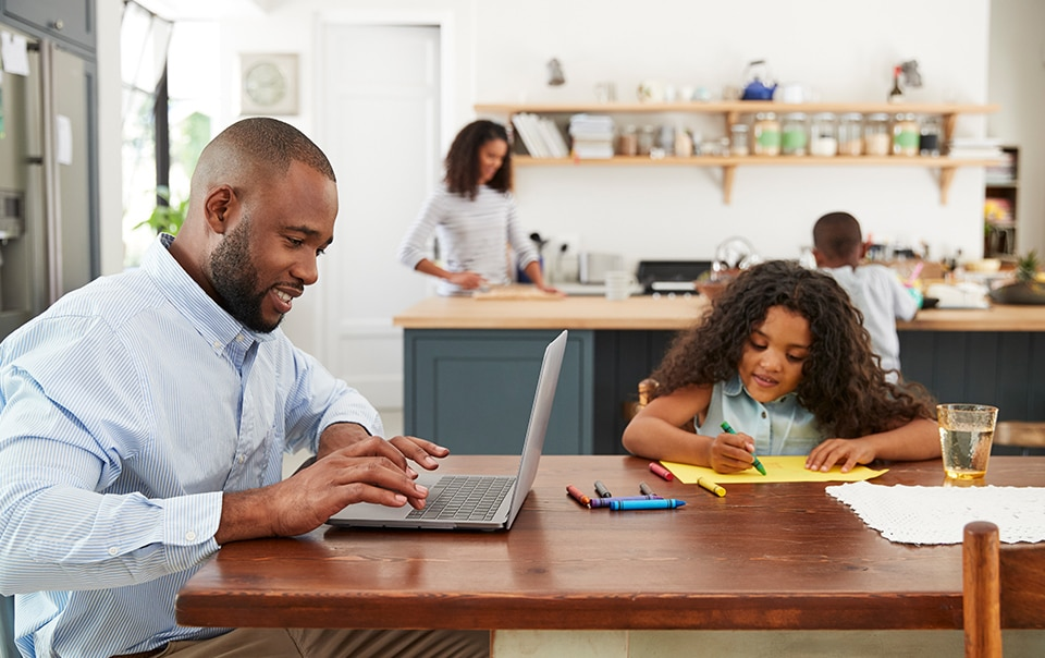 Father and daughter working together at kitchen table