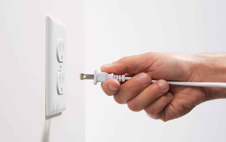 Person plugging cord into an outlet