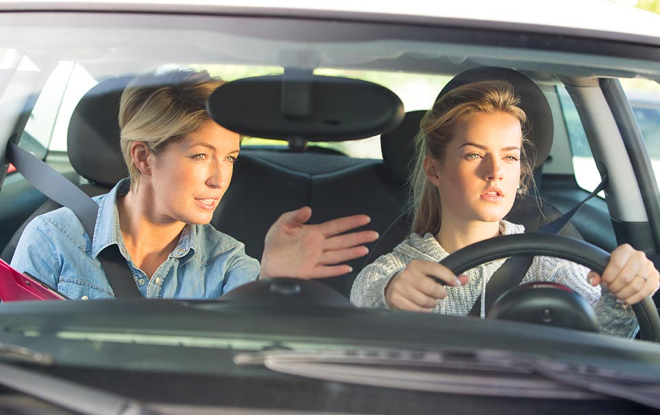 Parent and teen driving behind the wheel