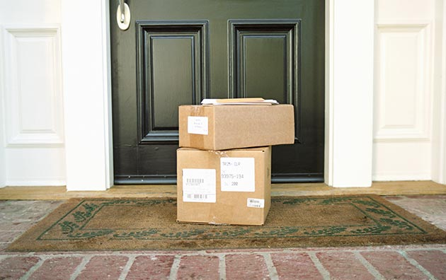 Brown boxes piled in front of a person's front door