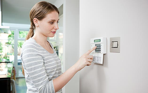 Women setting home security alarm