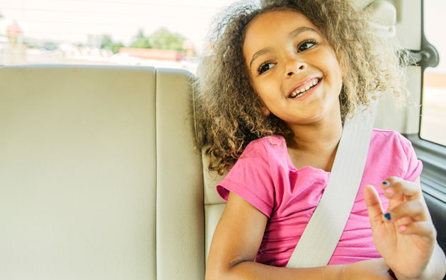 Young passenger sitting safely in the back seat of a car