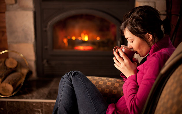 Woman drinking coffee beside fireplace