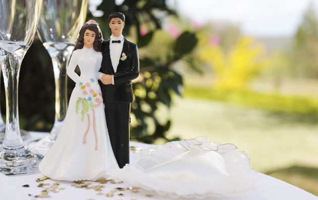 Cake topper of married couple on a table