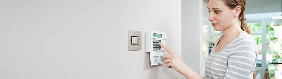 Woman setting home security alarm