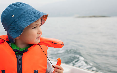 Child in a life jacket on a boat