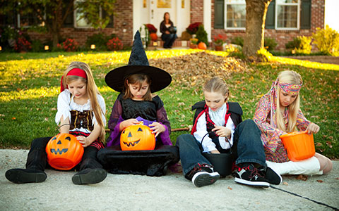 Four kids in Halloween costumes
