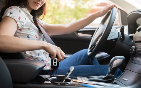 woman behind the wheel of her car putting her cell phone in the center console, 7 Common Car Accidents and How to Help Avoid Them