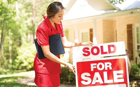 female real estate agent puts sold sign on home for sale sign; 10 reasons why you need a real estate agent